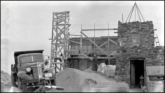 Construction of second (present) lookout on Mount Washburn, August 25, 1939.  Note first (stone) lookout building still standing in foreground.
